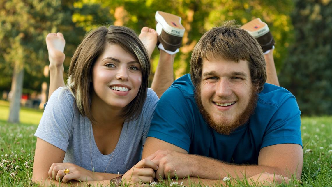 Couple Facing Camera On Grass